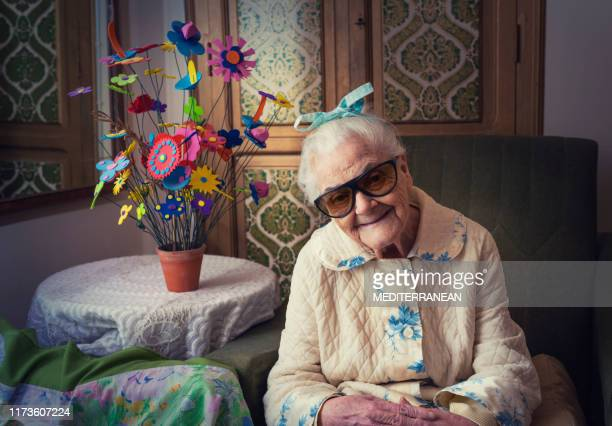 elderly 90s old woman portrait sitting in armchair - 100th anniversary stock pictures, royalty-free photos & images