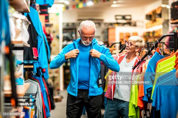 elderly active man trying on a soft shell hiking jacket while his partner is watching in an outdoor equipment store - sports equipment stock pictures, royalty-free photos & images