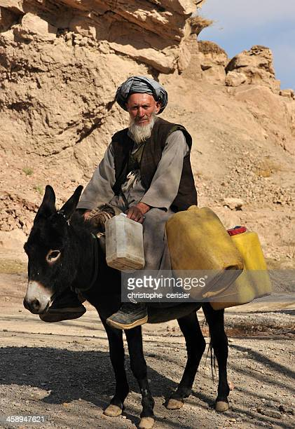 Elderly Afghanistan man with gray beard and turban on donkey
