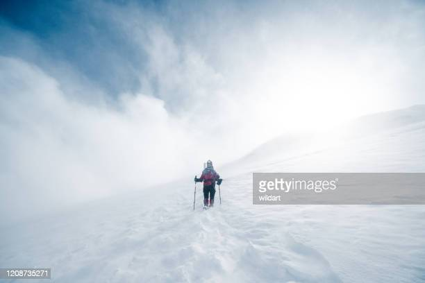 elderly alpine mountain climber is climbing to the peak of high altitude mountain in winter - blizzard stock pictures, royalty-free photos & images