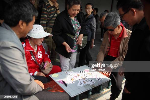 Elderly and retired Chinese people play cards for fun in the Temple of Heaven compund Beijing China April 25 2016