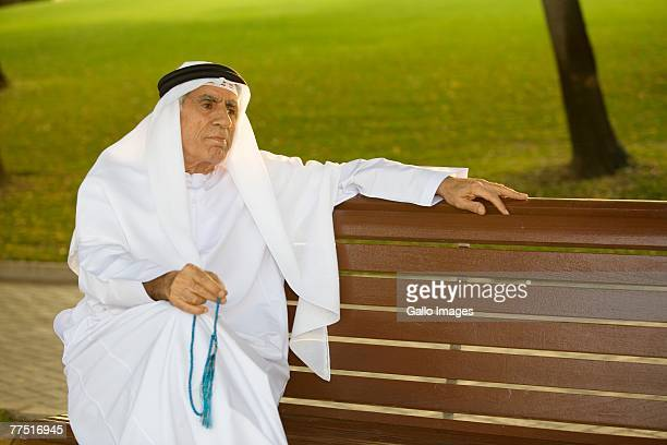 Elderly Arabic Man Sitting on Bench with Prayer Beads in Park. Dubai, United Arab Emirates