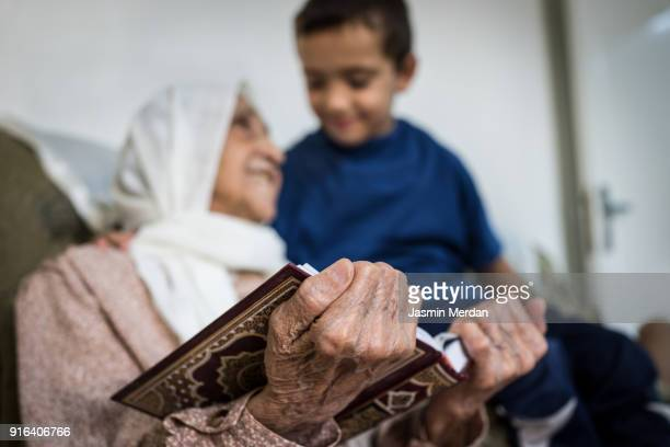 Elderly Arabic woman with grandson sitting and reading holy book Koran