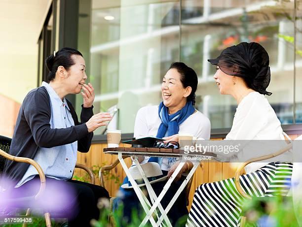 アジアの老人女性に話すのゴシップには、屋外カフェ