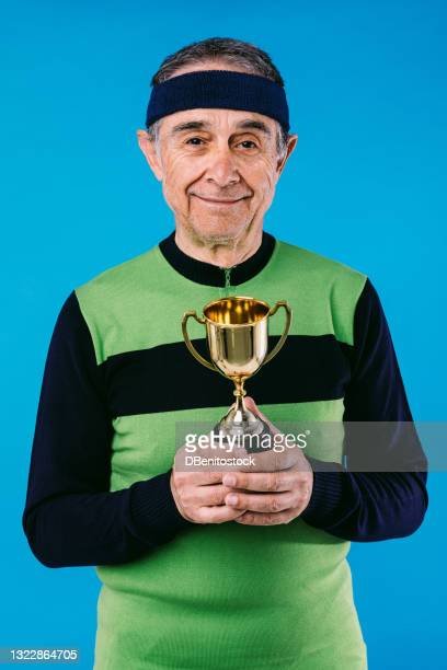 elderly athlete in green and black vintage jersey with a trophy cup in his hands on blue background. - third place stock pictures, royalty-free photos & images