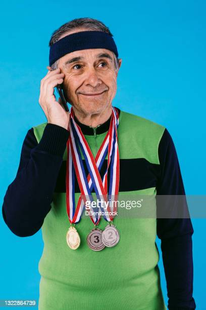 elderly athlete wearing a green and black vintage jersey, with 3 hanging medals, talking on the phone, on a blue background. - third place stock pictures, royalty-free photos & images