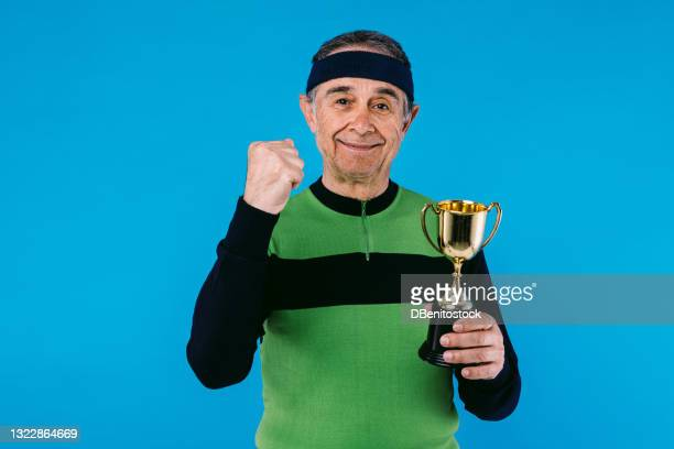 elderly athlete wearing green and black vintage jersey, clenching a fist and holding a trophy cup in his hands on blue background. - third place stock pictures, royalty-free photos & images