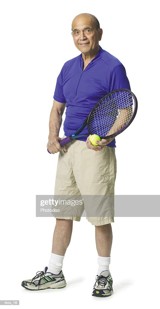 Elderly balding man wearing a blue shirt and holding a tennis racket smiling at the camera. : Foto de stock