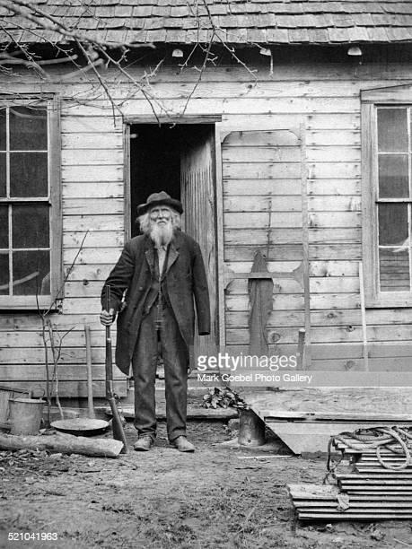 Elderly bearded man with gun 1910s