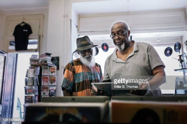 elderly black friends searching record bin - afro caribbean ethnicity stock pictures, royalty-free photos & images