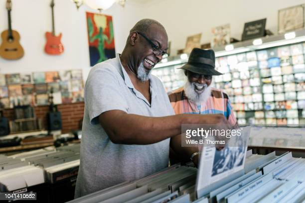 elderly black friends searching record bin - disruptagingcollection stock photos and pictures