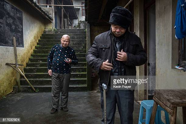 Elderly blind Chinese resident Chen Guoqingleft listens to his radio as another residents walks out of his room in the old temple area at the Ji...