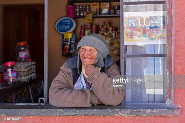 Elderly Bolivian woman, female vendor looking through shop window in the city Uyuni, Antonio Quijarro Province, Potosí Department, Bolivia.