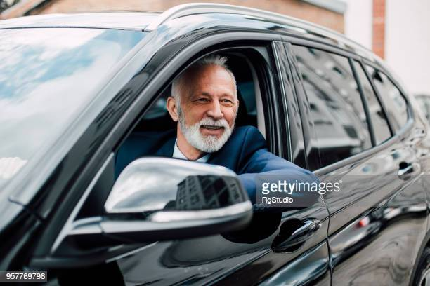 elderly business man in a car - prestige car stock pictures, royalty-free photos & images