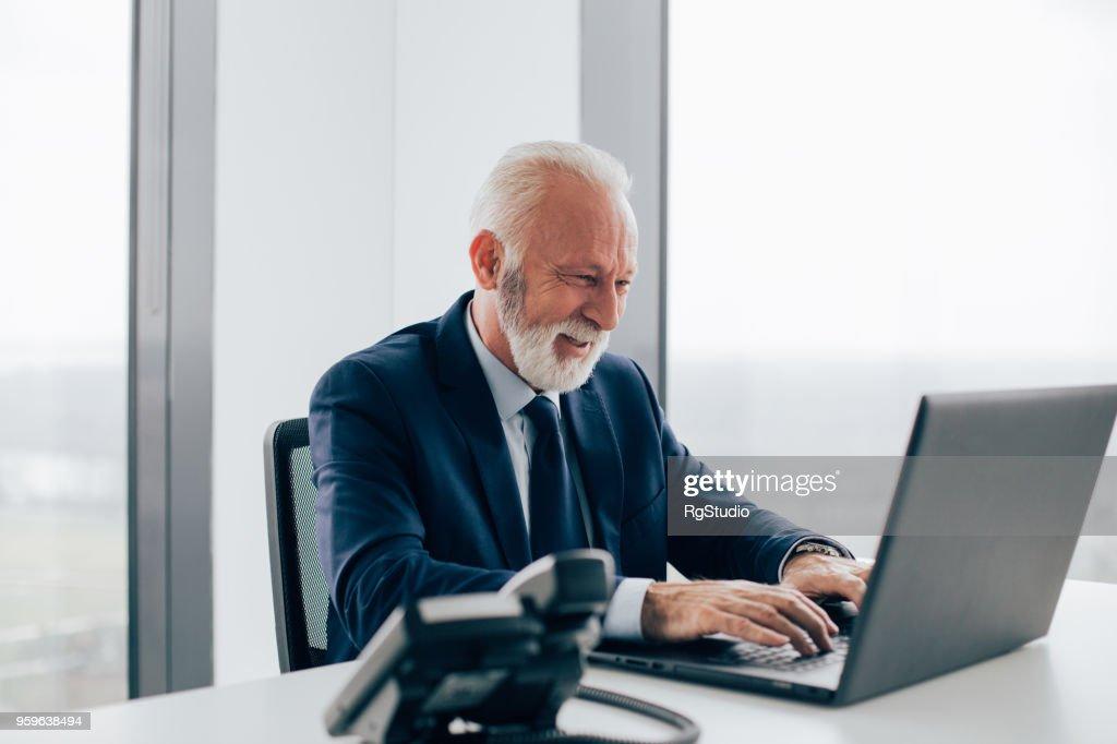 Älteren Geschäftsmann mit Laptop und lächelnd im Büro : Stock-Foto