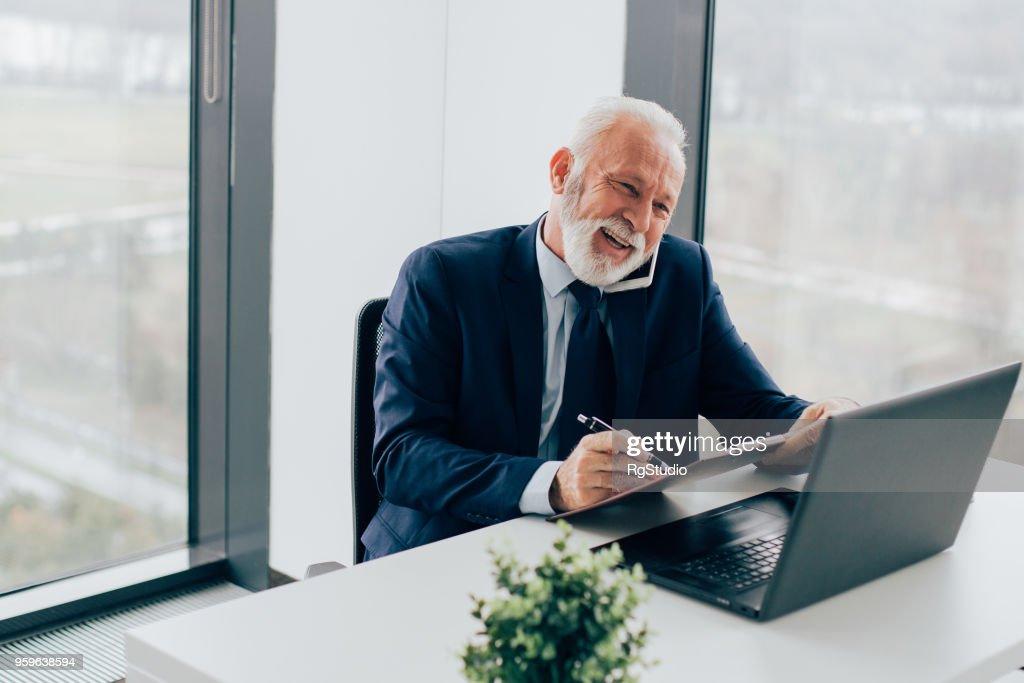 Ältere Geschäfte am Telefon sprechen und schreiben : Stock-Foto