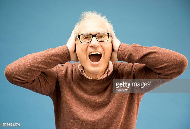 Elderly businessman shouting happily against blue background