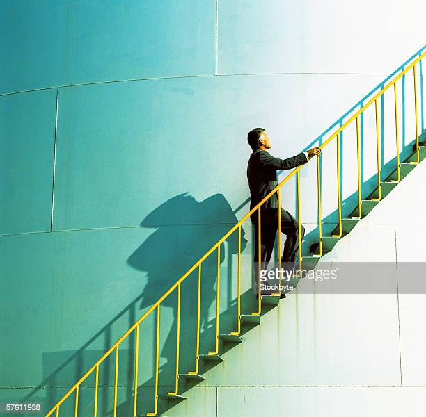 Elderly businessman walking up the stairs of a storage tank