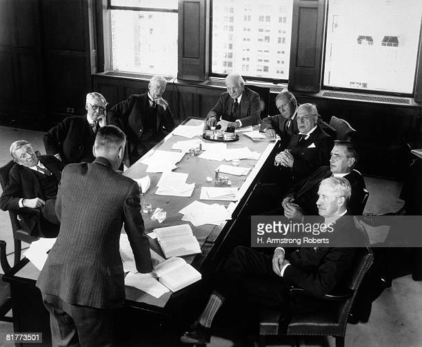 Elderly Businessmen At Conference Table With 1 Man Standing & Talking