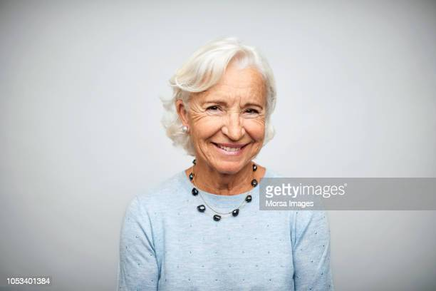 elderly businesswoman smiling on white background - seniore vrouwen stockfoto's en -beelden