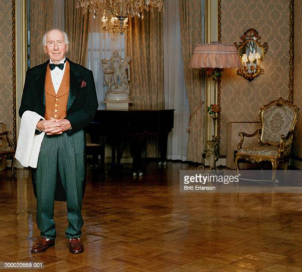 elderly butler standing in room, portrait - butler stock pictures, royalty-free photos & images