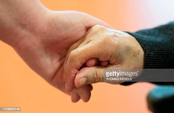 Elderly care nurse holds the hand of a resident in the retirement home St. Barbara of German welfare organisation Caritas in Stuttgart, southern...