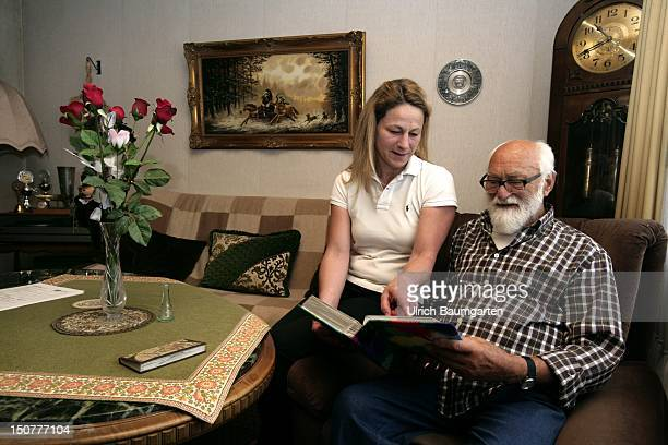 GERMANY Elderly care nurse in the home of an old man Our picture shows together view a photo album