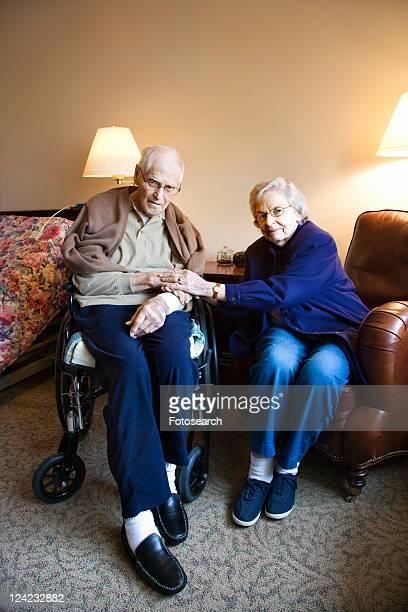 Elderly Caucasian couple in bedroom at retirement community center.