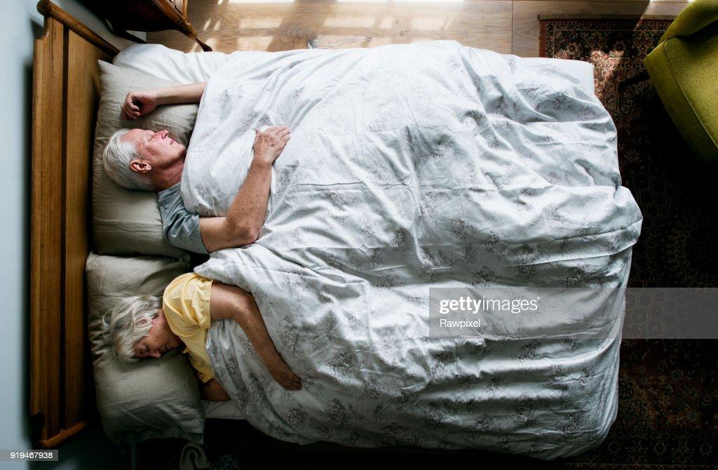 Elderly Caucasian couple sleeping on the bed : Stock Photo