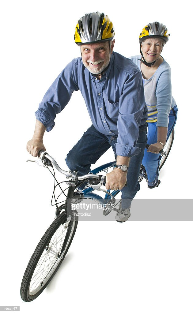 Elderly caucasian couple smile as they ride a tandem bike. : Foto de stock