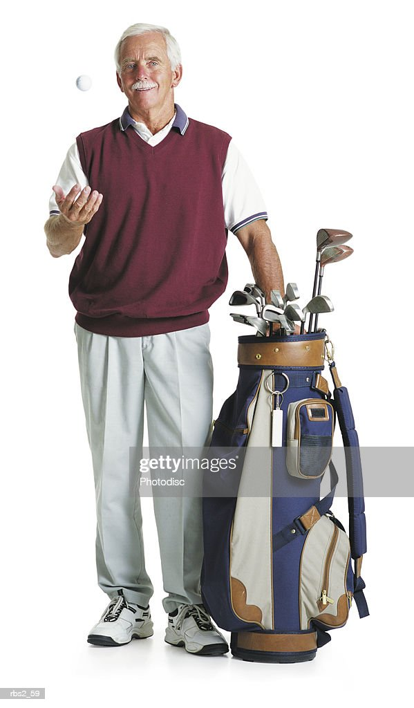 elderly caucasian man moustache wears maroon vest white slacks stands by golf bag tosses a golf ball : Foto de stock