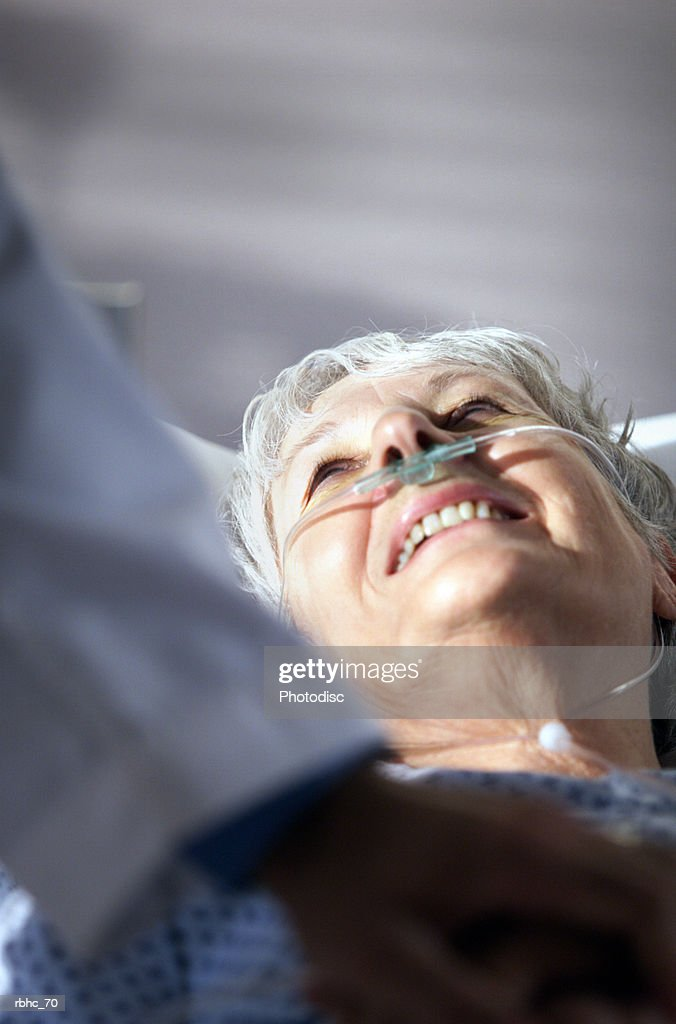 elderly caucasian woman looks up and smiles at doctor who has come to visit her in hospital room : Stockfoto