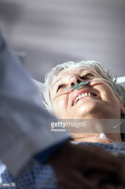 elderly caucasian woman looks up and smiles at doctor who has come to visit her in hospital room