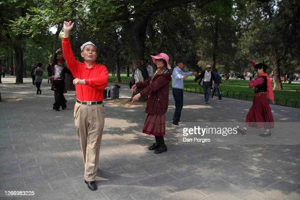 Elderly Chinese men and women dance for fun in the park at the Temple of Heaven compund Beijing China April 25 2016