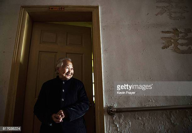Elderly Chinese resident Chen Minying stands outside her room at the Ji Xiang Temple and nursing home on March 18 2016 in Sha County Fujian province...