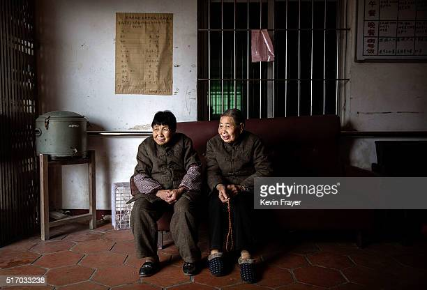 Elderly Chinese residents chat as they wait for a meal at the Ji Xiang Temple and nursing home on March 17 2016 in Sha County Fujian province China...