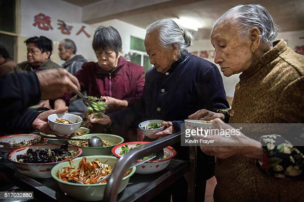 Elderly Chinese residents serve themselves food during a meal at the Ji Xiang Temple and nursing home on March 17 2016 in Sha County Fujian province...