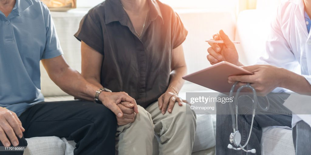Elderly couple, ageing senior patients having exam and family consultation in clinic with doctor, physician or therapist on menopause illness, mental health care, and geriatric syndrome screening : Stock Photo