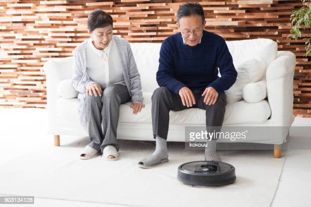 Elderly couple and robot vacuum cleaner.