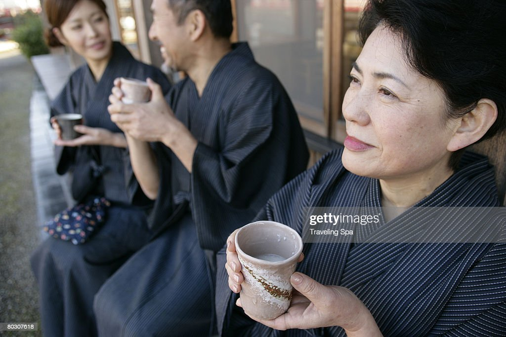 Elderly couple and young woman relaxing outdoor, holding cups : Stock Photo