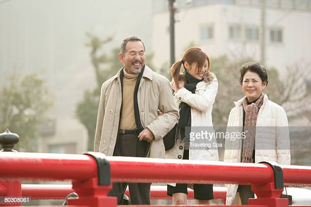 Elderly couple and young woman walking on a bridge, laughing, close-up