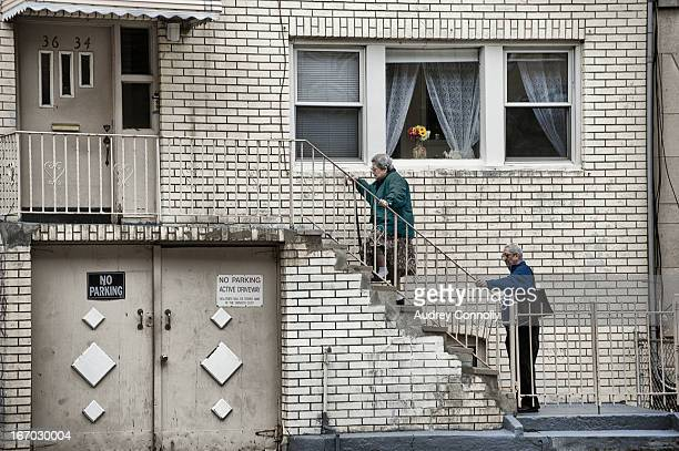 CONTENT] elderly couple ascend the steps of their two story home in Astoria Queens New York City