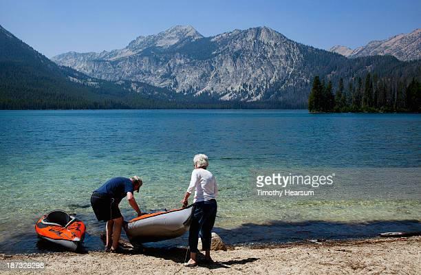 elderly couple carries kayak into pristine lake - timothy hearsum photos et images de collection
