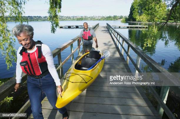 Elderly couple carrying a kayak walking on a pier