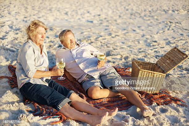 Elderly couple drinking white wine while at the beach
