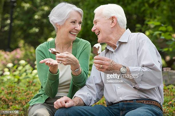 Elderly couple eating ice cream and smiling