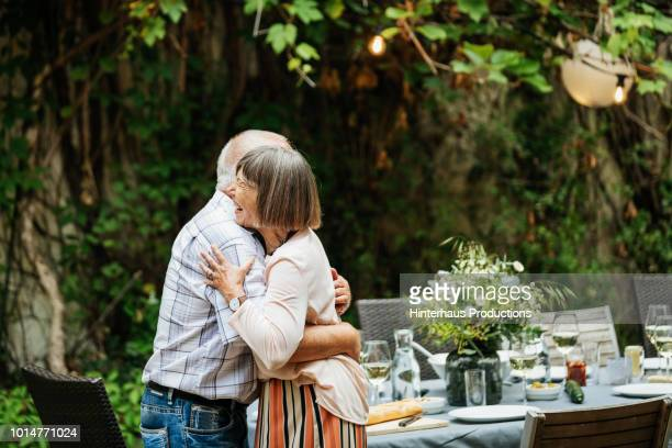 elderly couple embracing after eating outdoors with family - bella ciao foto e immagini stock