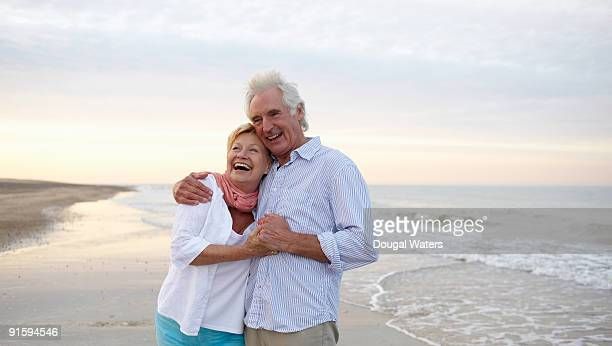 elderly couple embracing at beach. - senior couple stock photos and pictures