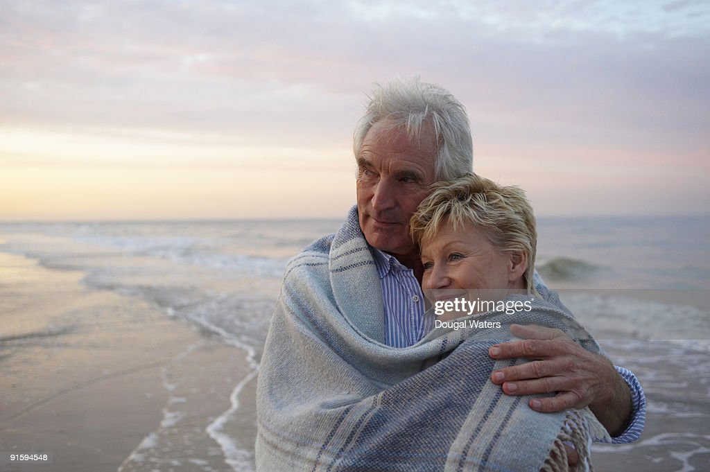 Elderly couple embracing at beach. : Stock Photo