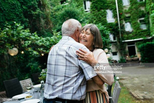 elderly couple embracing before bbq with family - senior couple stock pictures, royalty-free photos & images